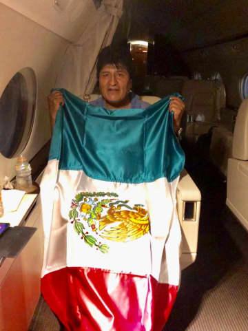 11日、メキシコ空軍機内で同国の国旗を掲げる、ボリビア大統領職辞任を表明したモラレス氏(メキシコ外務省提供、ロイター=共同)