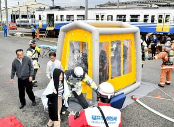 除染活動を行う消防隊員ら=11月11日、福井県福井市松本上町のえちぜん鉄道車両基地