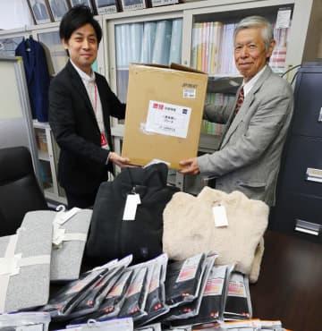 ユニクロの担当者(左)から白木会長に手渡された冬物衣料