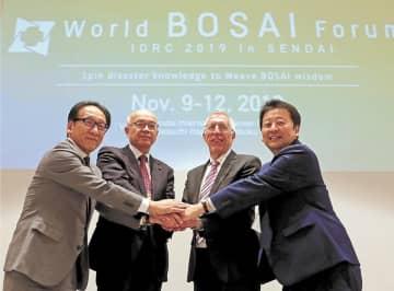 クロージングセッションで手を取り合う(左から)今村実行委員長、高橋新悦仙台市副市長、バシャー議長、小野代表理事