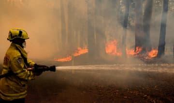 12日、オーストラリア東部ニューサウスウェールズ州で発生した森林火災で放水する消防士(ロイター=共同)