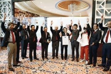 熊本開催が決まり喜ぶ県関係者ら=2013年10月、カタール・ドーハ
