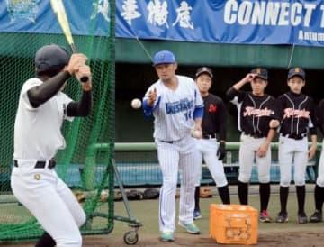 バッティングの指導をする戸柱恭孝捕手(中央)=奄美市の名瀬運動公園
