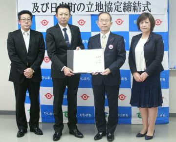 立地協定締結式に出席したルートインジャパンの永山泰樹社長(左から2人目)と本田博文日出町長(同3人目)ら=13日、日出町役場