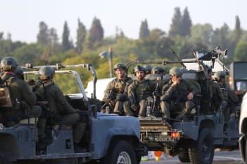 13日、ガザに隣接するイスラエル南部スデロトで、路上に展開するイスラエル軍兵士ら(ゲッティ=共同)