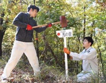 手作りの道標を設置する地域おこし協力隊の佐藤さん(左)と高橋さん