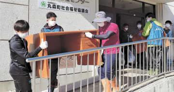 水に漬かった机を運び出す学生ボランティア