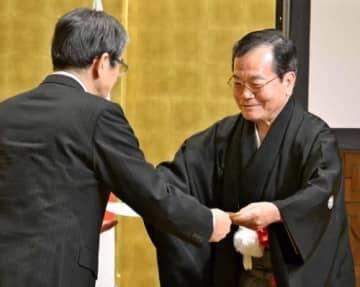 宮田亮平文化庁長官(左)から人間国宝認定書を受け取る中村一雄さん=13日、東京・丸の内の東京会館