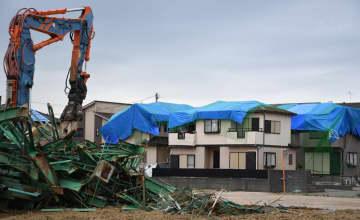 ゴルフ練習場の倒れた鉄柱が撤去された住宅。雨水から守るためにブルーシートと固定ネットが張られた=13日午後、市原市五井