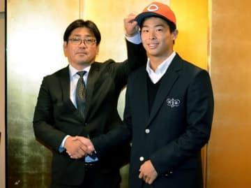 高山健一スカウト(左)から帽子をかぶせてもらい笑顔の玉村昇悟=11月13日、福井県福井市のユアーズホテルフクイ