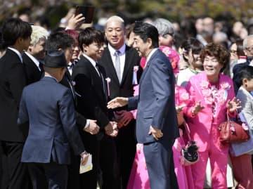 「桜を見る会」で招待客と握手を交わす安倍首相(中央)=4月、東京・新宿御苑