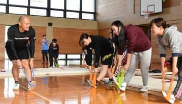秋田さん(左)から筋力トレーニング方法について学ぶ学生
