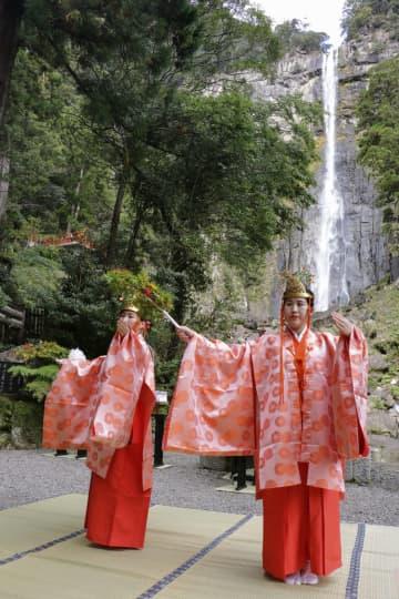 熊野那智大社のご神体「那智の滝」前で神楽を披露するみこ=14日、和歌山県那智勝浦町