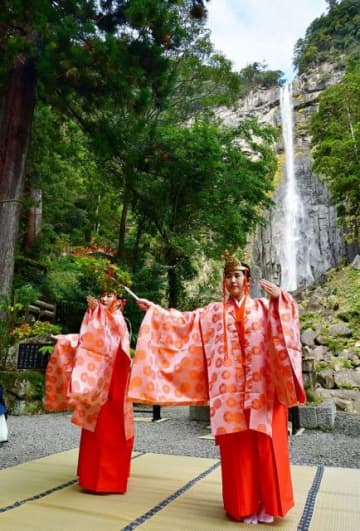 モミジの枝を持ち、那智の滝の前で舞を奉納するみこ(14日、和歌山県那智勝浦町那智山で)