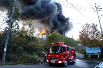 黒煙を上げて燃える作業所の消火に当たる消防隊員(14日午後1時19分)