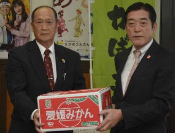 中村時広知事(右)に支援物資のミカンを贈呈するJAえひめ南の山本長雄組合長=14日、県庁