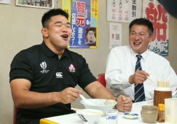 大好きだったチャーシューメンを食べて笑顔を見せる具智元選手(左)と高校時代の恩師・染矢勝義さん=14日午後、佐伯市内町