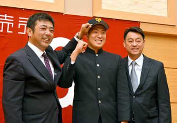 仮契約を終え、巨人の帽子をかぶって柏田貴史スカウト(左)らと笑顔を見せる伊藤海斗外野手(中央、酒田南高)=遊佐町・遊楽里