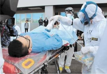 けが人の放射線量を測定する訓練に取り組む職員