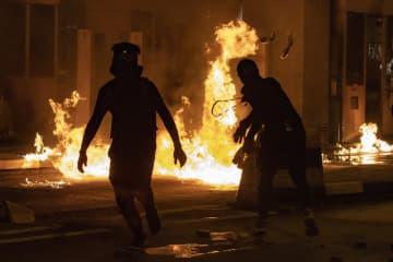 14日、九竜半島と香港島を結ぶ海底トンネルの料金所に火炎瓶を投げる若者(AP=共同)