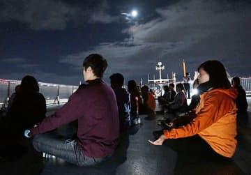 月明かりに照らされて瞑想する参加者たち=12日夜、大阪市阿倍野区のあべのハルカス