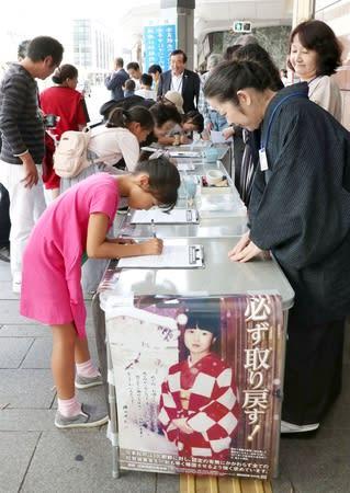 拉致被害者の早期帰国に向けて県民らに協力を求めた署名活動。ペンをとる子どもの姿もあった=6日、新潟市中央区
