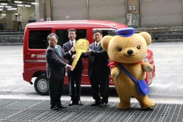 左から三菱自動車の若林陽介執行役員、日本郵便の上尾崎幸治執行役員、生島顕一銀座郵便局長、そしてマスコットの「ぽすくま」君