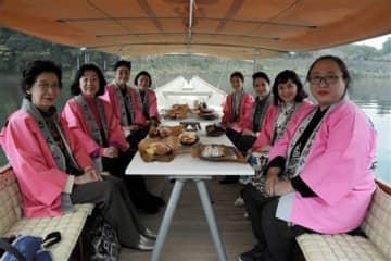 新型舟に設置されたテーブルに弁当を並べてランチを楽しむさくら会のメンバー=人吉市