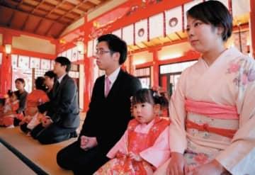 七五三で祝詞を上げてもらう子ども連れの家族=15日午前、大分市の春日神社