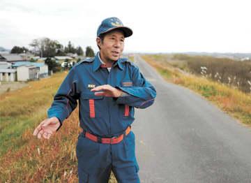 吉田川左岸の堤防上で、台風19号襲来時の消防団の活動を説明する分団長の佐藤さん=大崎市鹿島台