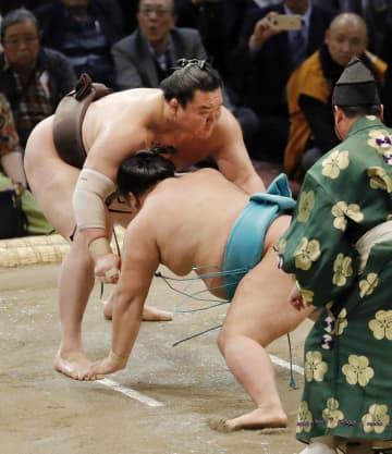 白鵬(左)が上手出し投げで明生を下す=福岡国際センター