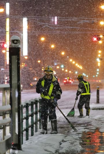 路面電車のレールを雪かきする人たち=15日早朝、札幌市中央区