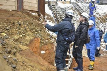 北海道電力泊原発の敷地内にある断層の試掘溝を視察する原子力規制委の石渡明委員(左から2人目)=15日、北海道泊村