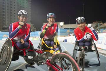 男子1500メートル(車いす)で表彰台を独占し、ガッツポーズする(左から)2位の上与那原寛和、1位の佐藤友祈、3位の伊藤智也=ドバイ(共同)