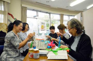包装袋作りに取り組む「はっぴー子育て応援団」のメンバーら