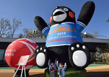 """女子ハンドボール世界選手権の開幕を控え、日本代表のユニホーム姿に""""衣替え""""した「サクラマチ クマモト」の巨大くまモン=15日午後、熊本市中央区"""