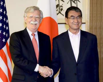 7月、日本の外務省で河野太郎外相(当時)と握手を交わすボルトン米大統領補佐官(当時)=東京