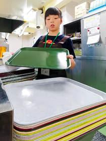 料理を運ぶトレーの表裏を拭く1年生