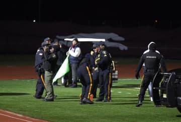 アメリカンフットボールの試合中の発砲事件を受け、高校のグラウンドで捜査を行う関係者=15日、プレザントビル(ザ・プレス・オブ・アトランティックシティー・AP=共同)