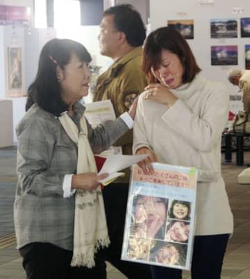 山梨県道志村で行方不明になった小倉美咲さんの情報提供を求めるチラシを配布中、通行人に励まされ涙する母とも子さん(右)=16日午後、JR甲府駅