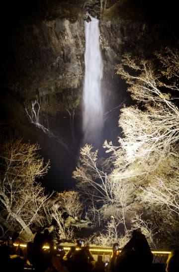 初めてライトアップされた日本三名瀑の一つ「華厳の滝」。暗闇の中に浮き上がり、観光客らを魅了した=16日夕、栃木県日光市