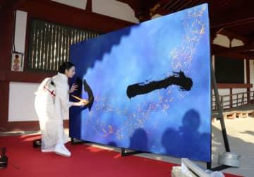 奈良・東大寺で揮毫する岡西佑奈さん=16日午後