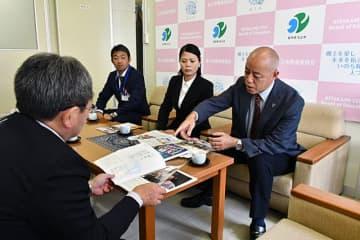 平野憲教育長に「多種目のススメ」を紹介する司東道雄理事長(右)