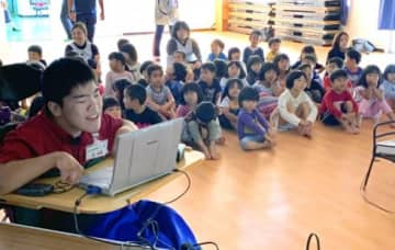 園児たちにパソコンを使って読み聞かせをする前和輝さん=伊仙町犬田布