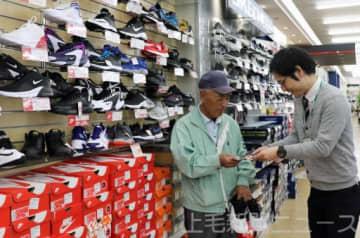 靴用の反射材シールを手渡す店員(右)=11月上旬、吉岡町