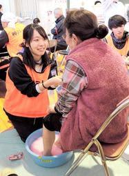 足湯を用意し、被災者の心身の疲れを癒やす神戸大の学生たち=16日午後、宮城県丸森町
