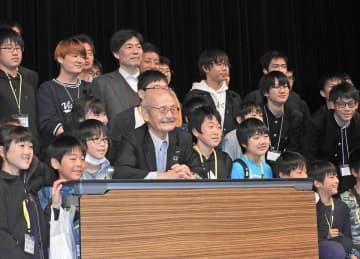 出展者との交流会で子どもらに囲まれ笑顔を見せる吉野彰さん(前列中央)=16日午後4時10分、岐阜市金町、市文化センター
