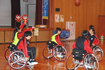 【車いすの乗りバスケットボール競技を体験する生徒ら=亀山市関町新所の市立関中学校で】