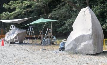 アーティストの制作工程を公開している石の彫刻祭会場=真鶴町真鶴の番場浦駐車場