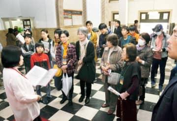ガイドから県庁本館の歴史など説明を受ける来場者=16日午前、松山市一番町4丁目